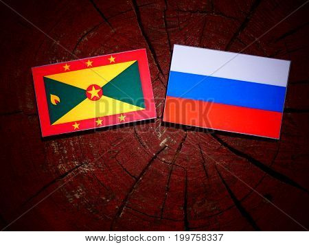 Grenada Flag With Russian Flag On A Tree Stump Isolated