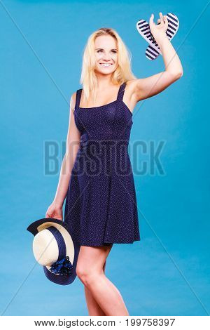 Summer trendy fashionable outfit ideas concept. Woman wearing short navy dress holding sun hat and flip flops