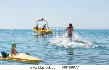 Young man glides on water skiing on the waves on the sea ocean. Healthy lifestyle. Positive human emotions feelings joy.