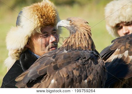 ALMATY, KAZAKHSTAN - SEPTEMBER 18, 2011: Portrait of unidentified Kazakh hunters holding golden eagles (Aquila chrysaetos) circa Almaty, Kazakhstan.