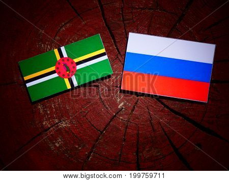 Dominica Flag With Russian Flag On A Tree Stump Isolated