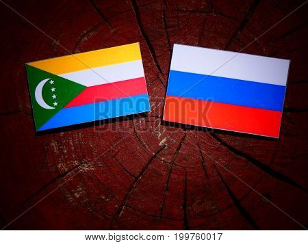 Comoros Flag With Russian Flag On A Tree Stump Isolated