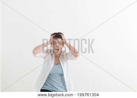 Headshot of hysterical Caucasian freckled student girl looking in despair and panic, being late for important exam or event, not knowing what to do, hands on her head, mouth wide open.