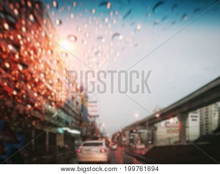 Blur street traffic in twilight after rain (Thailand); wet car glass (clear with blue color on top) from raindrops and dried part from windshield wiper. Sky-train rail on the right. Top copy-space.