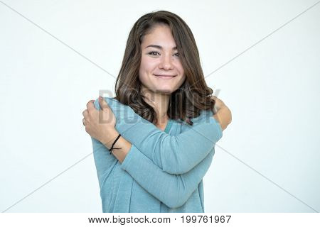 Happy caucasian woman in blue shirt hugging herself with natural emotional enjoying face