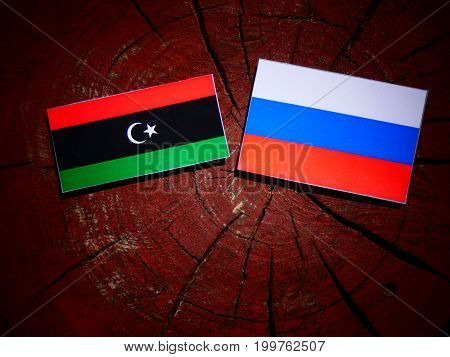 Libyan Flag With Russian Flag On A Tree Stump Isolated