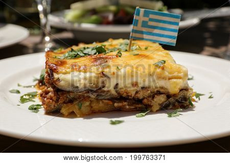 Traditional moussaka with eggplants, ground beef and potatoes in greek tavern. Horizontal. Daylight. Close-up.