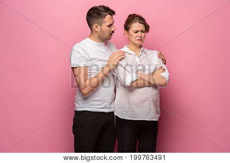 The funny handsome man and his beautiful pregnant wife at pink studio background. quarrel concept