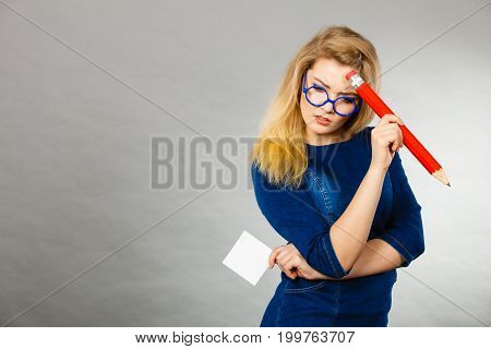Confused Woman Holds Big Pencil Note Paper In Hand