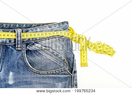 Healthy lifestyle and dieting concept. Blue jeans with yellow measure tape instead of belt. Upper part of denim trousers isolated on white background. Close up of jeans with measure tape around waist.
