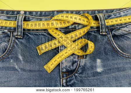 Blue jeans with yellow measure tape instead of belt. Top part of denim trousers isolated on yellow background. Healthy lifestyle and dieting concept. Close up of jeans with measure tape around waist.
