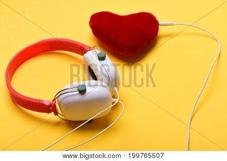 Headset for music and heart shaped player. Headphones in white and red color with soft heart. Modern and stylish earphones isolated on orange background. Music accessories and Valentines day concept