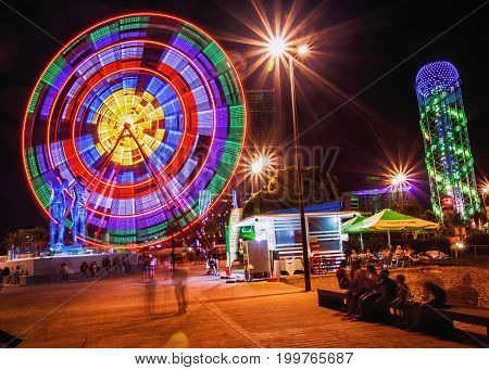 Batumi, Adjara, Georgia. Ferris Wheel At Promenade In Miracle Park, Amusement City On Night Time