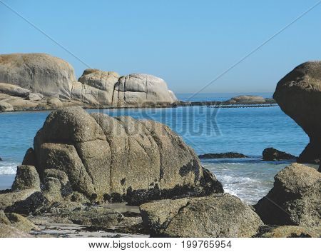 FROM CAMPS BAY  CAPE TOWN, SOUTH AFRICA, HUGE BOULDERS IN THE FORE GROUND AND THE BACK GROUND