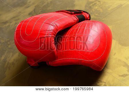 Sport Equipment Golden Beige Pattern Background. Boxing Gloves In Red
