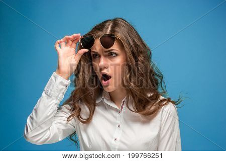 The portrait of young surprised woman with shocked facial expression