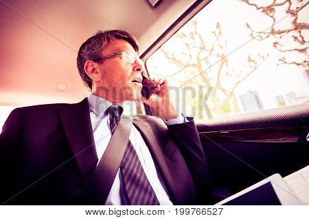 businessman on the road, sitting in the back of a car