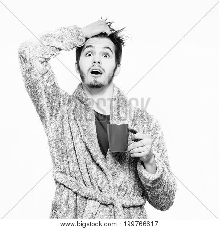 handsome surprised man or bearded sexy guy in blue terry bathrobe or dressing gown holds coffee or tea cup isolated on white background copy space