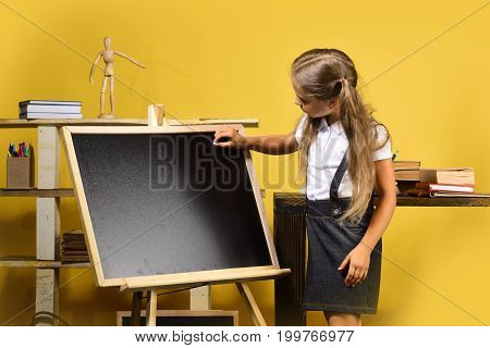 Schoolgirl With Busy Face And Ponytails Stands In Classroom