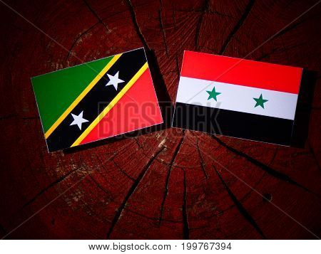 Saint Kitts And Nevis Flag With Syrian Flag On A Tree Stump Isolated