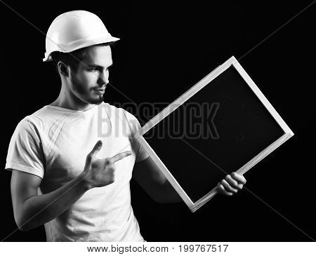 handsome bearded builder or foreman in white shirt and helmet on serious face holding board on black studio background copy space