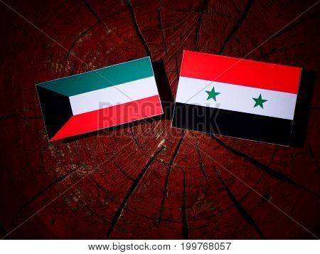 Kuwaiti Flag With Syrian Flag On A Tree Stump Isolated