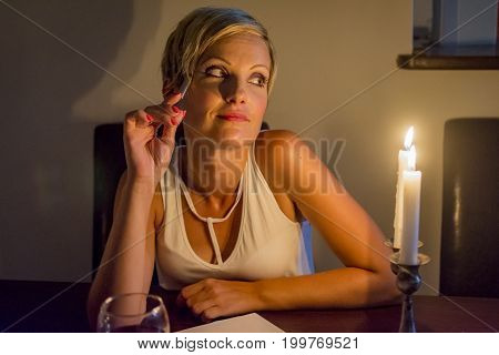 woman in love writing a letter under candle light