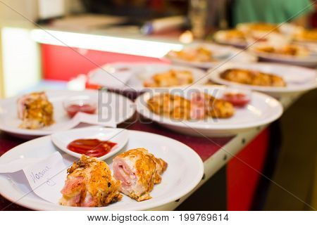 Fried meat rolls in a white plate on a bar rack.