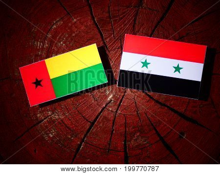Guinea Bissau Flag With Syrian Flag On A Tree Stump Isolated