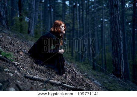 Woman in a black long dress is sitting in a dark forest.