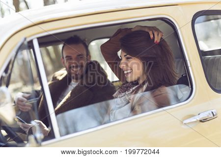 Young couple having fun and enjoying a road trip. Girl driving a car while the guy is sitting and laughing