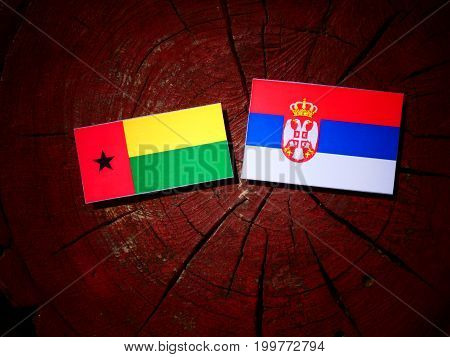 Guinea Bissau Flag With Serbian Flag On A Tree Stump Isolated