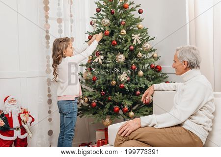 Grandfather And Granddaughter Decorating Christmas Tree