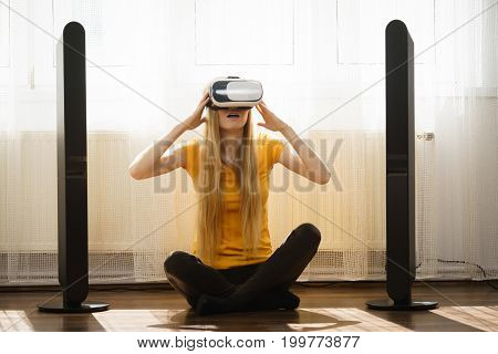 Young woman wearing virtual reality goggles vr box with arms outstretched sitting on floor in living room listening to music. Connection technology new generation and progress concept.