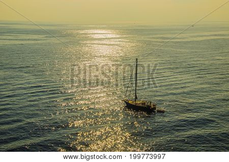 Sunset and sailboat accompanied by his boat in peaceful waters in the Tyrrhenian Sea