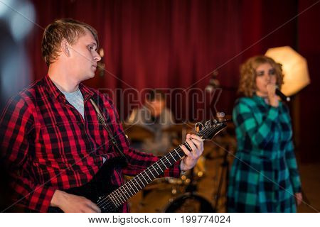 The guitarist plays the guitar and vocalist screeming at a concert