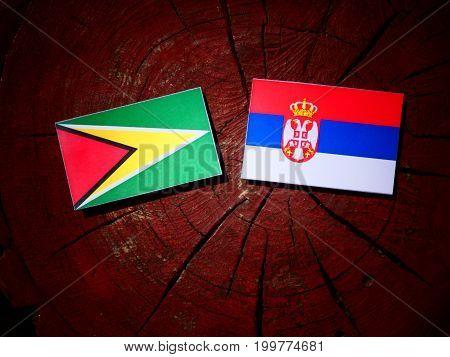 Guyana Flag With Serbian Flag On A Tree Stump Isolated