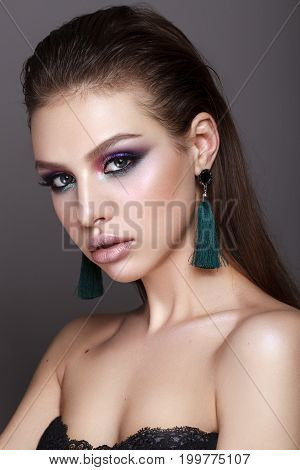 Beautiful young model with fashion make up, perfect skin, long earrings and wet hair. Trendy colorful smoky eyes.