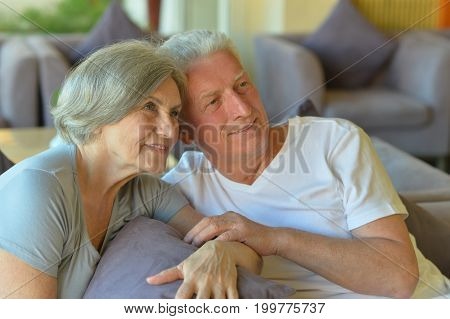 Portrait of a happy senior couple sitting on couch