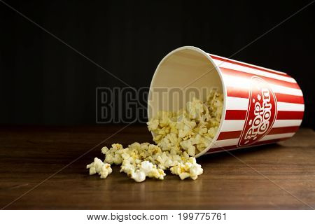 Popcorn on wooden table with clipping path .Red and white striped  box of popcorn for movie ,Word of popcorn on the bucket