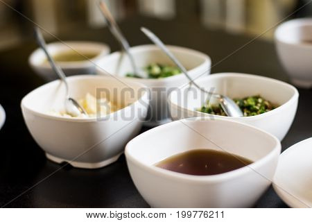Chinese sukiyaki sauce in little bowl on black table.Ssauce for dipping meat and vegetable. Chinese sauce for adding flavor to sukiyaki and shabu shabu.