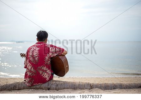 Handsome man playing classic guitar sitting on the beach in vacations. Summer Concept