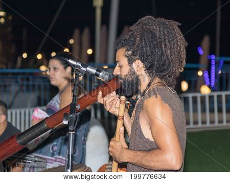 Nahariya Israel August 14 2017 : A young guy plays a big pipe in the evening on the waterfront in the city of Nahariya in Israel
