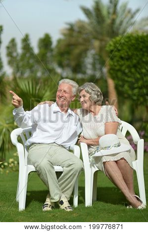 Happy senior couple sitting on plastic chairs outdoors