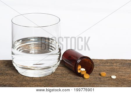 Medications in a container and a glass of water