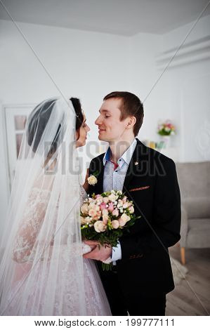 Beautiful Wedding Couple Kissing And Looking Into Each Other's Eyes In The Studio.
