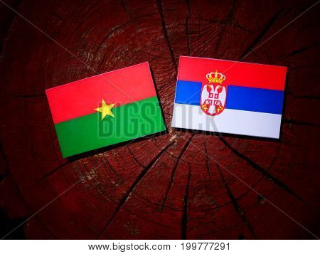 Burkina Faso Flag With Serbian Flag On A Tree Stump Isolated