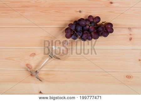 Empty wine glass with red grape on wooden background