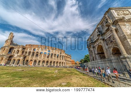 ROME ITALY - MAI 30 2017: View of the arch of Constantine and the Coliseum in Rome Italy with a lot tourists. Sky with clouds in background.