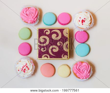 Macaroons cupcakes and gift box on beige background. Top view